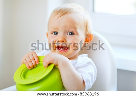 Adorable baby sitting in baby chair and playing with plate