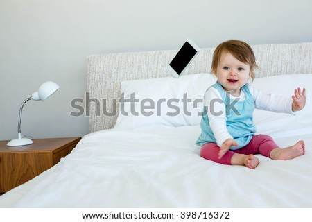 adorable baby sitting on a bed, throwing a mobile phone - stock photo