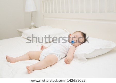 Adorable baby sleeping relaxed and sprawl in parent's bed - stock photo