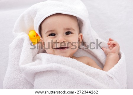 Adorable baby smiling wrapped in white towel with yellow duck, isolated on white