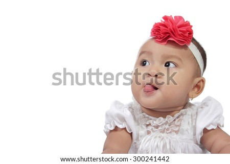 Adorable baby sticking her tongue out looking at copy space, isolated on white background