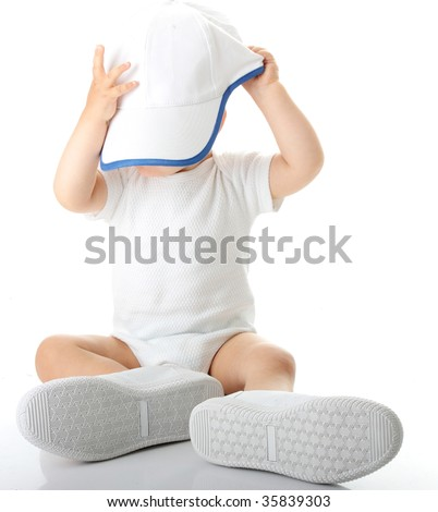 Adorable baby trying on shoes and basebal cap that are way too big for him - stock photo