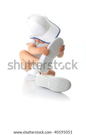 Adorable baby trying on shoes and baseball cap that are way too big for him - stock photo