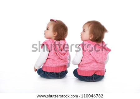 Adorable baby twin girl sisters wearing blue jeans and pink tops with pretty bows in their hair isolated on a white seamless background