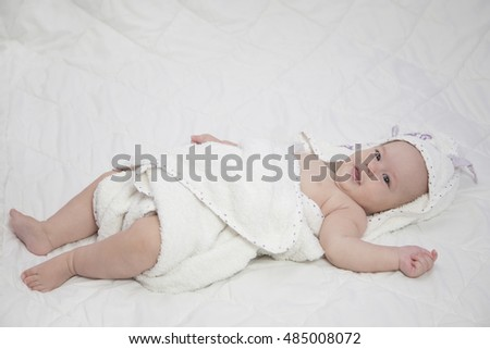 Adorable  baby under a white blanket/towel .Nursery for young children. Textile and bedding for kids