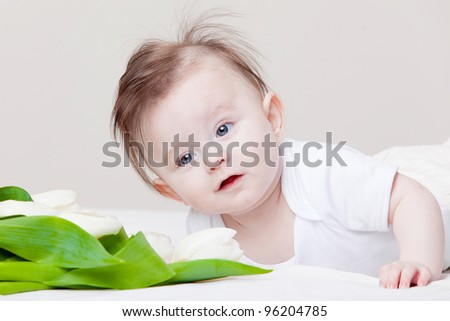 Adorable baby with bouquet of white tulips