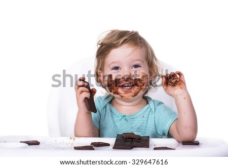 Adorable baby with face covered in chocolate - stock photo