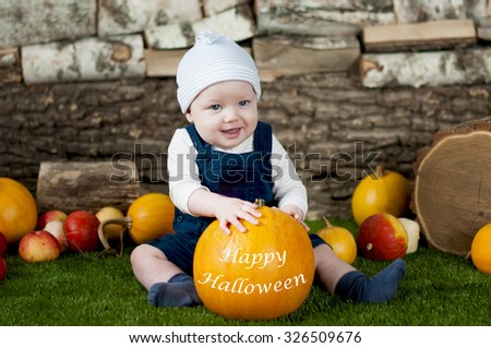 Adorable baby with many different pumpkins on grass over wooden background.