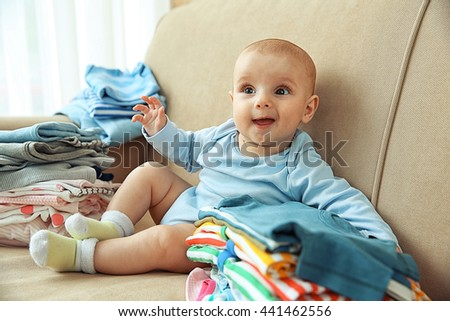 Adorable baby with piles of clothes on sofa in the room - stock photo