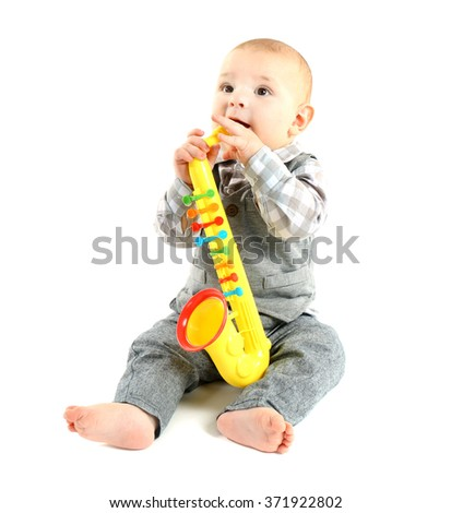 Adorable baby with plastic colourful saxophone isolated on white background - stock photo