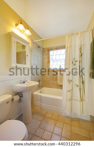 Adorable bathroom in ivory tones with wash basin stand, bathtub and nice curtain. - stock photo