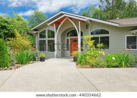 Adorable beige house with white trim, walkway and flower bed.  - stock photo