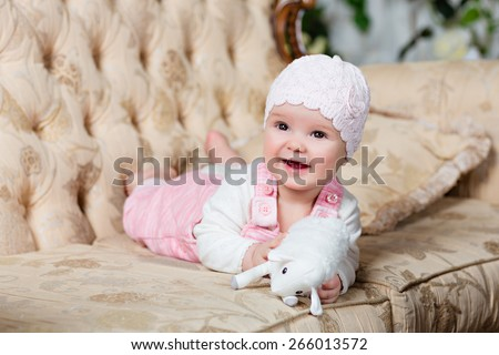 adorable big-eyed little girl in a pink jumpsuit smiles and lies on the couch in the interiors of the Studio, holding in her hands a toy sheep - stock photo