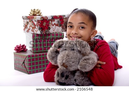 Adorable biracial girl hugging a stuffed animal and sitting next to a pile of wrapped Christmas presents.