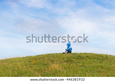 adorable blond baby toddler wearing blue clothing playing outdoors on rural field with bright green grass and blue sky  - stock photo