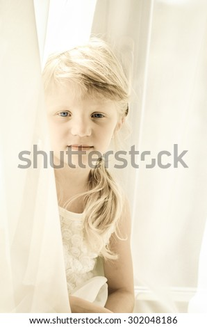 adorable blond child with long hair among white curtain filtered desaturated effect - stock photo
