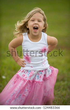 Adorable blond girl outside at the park wearing a tutu outfit - stock photo