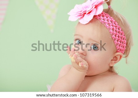 Adorable blond hair big blue eyed baby girl with pink flower elastic head band on head and pony tail in hair sucking eating and tasting vanilla sponge cake on green background with flag bunting behind