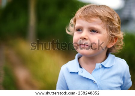 Adorable blond kid boy of 3 years walking in nature on a country road , outdoors. - stock photo