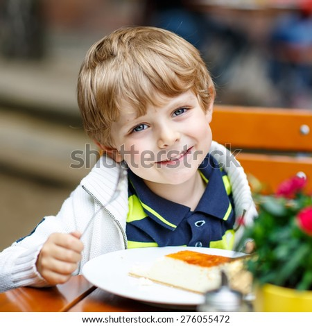 Adorable blond little kid boy, laughing and eating cake in an outside cafe in summer in an old city center in Germany on warm summer day.