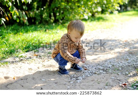 Adorable blond toddler boy in warm sweater playing outdoors
