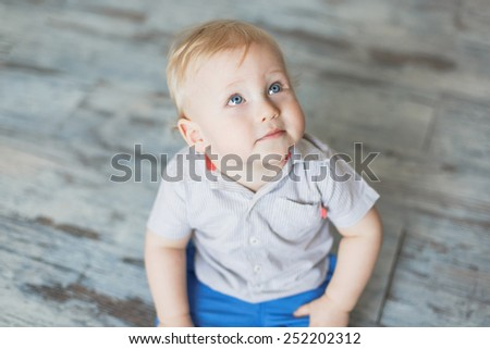 adorable blonde baby boy sitting on the floor and looking at something with curiosity - stock photo