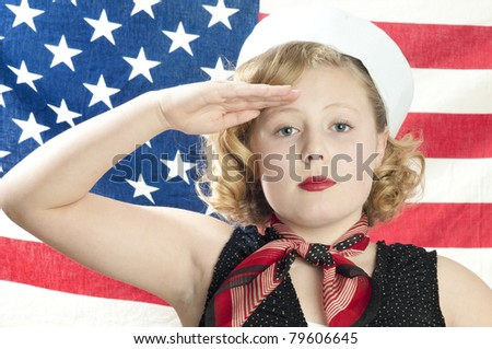 Adorable blonde girl model saluting in front of American flag - stock photo