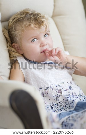 Adorable Blonde Haired and Blue Eyed Little Girl Sitting in Chair.