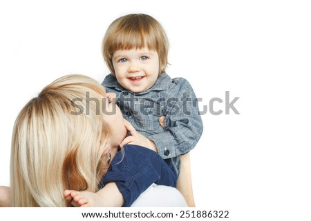 adorable blue eyed baby boy sitting on mother's shoulders and smiling over white background - stock photo
