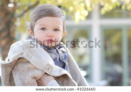 Adorable blue eyed baby boy wearing a fall coat outdoors - stock photo