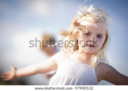 Adorable Blue Eyed Girl Playing Outside with Her Family. - stock photo