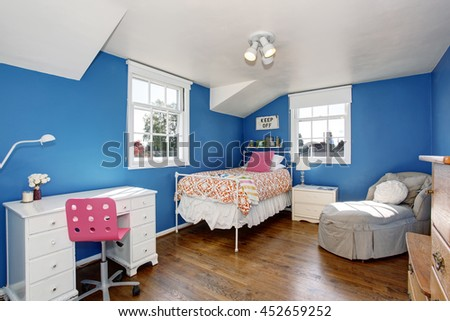 Adorable blue kids room with hardwood floor and vaulted ceiling. Furnished with small iron bed, white desk with drawers and comfortable armchair.