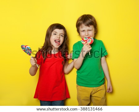 Adorable boy and girl in different moods while licking lollipops, on yellow background - stock photo