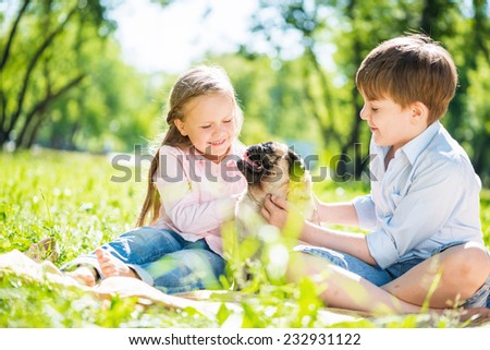 Adorable boy and girl in summer park with their dog - stock photo