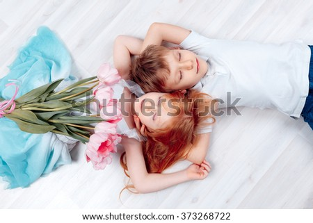 Adorable boy and girl lying on the floor with a bouquet of tulips. Mother's Day, 8 March, the birthday, the International Women's Day - stock photo