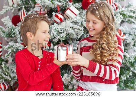 Adorable boy and girl opening presents on Christmas day