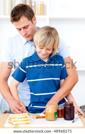 Adorable boy and his father preparing breakfast  in the kitchen - stock photo