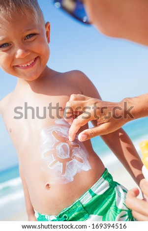 Adorable boy and mother at tropical beach applying sunblock cream. - stock photo