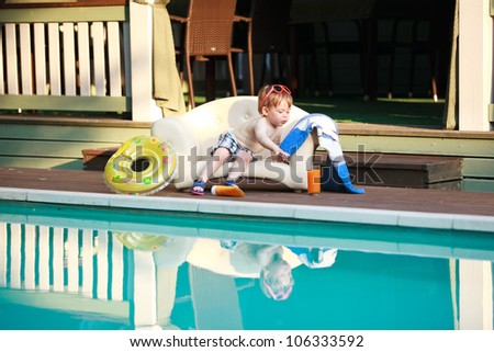 Adorable boy at the swimming pool - stock photo