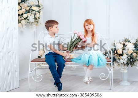adorable boy gave the girl a bouquet of flowers, 8 March, a happy birthday - stock photo