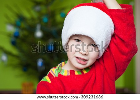 Adorable boy in a Christmas costume on a background of the Christmas tree - stock photo