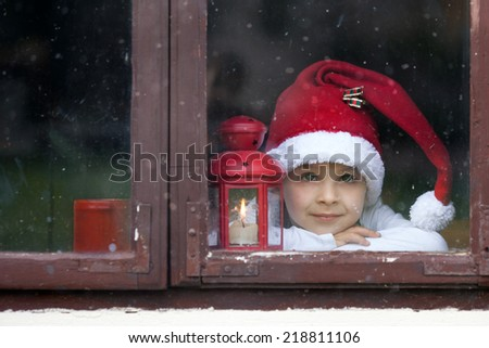 Adorable boy, looking through window, waiting for Santa - stock photo