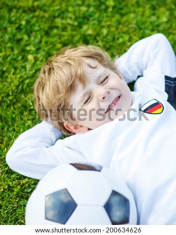 Adorable boy of 4 resting after playing soccer with football on football field, outdoors. - stock photo