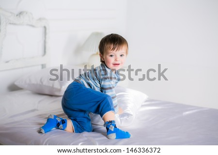adorable boy on a bed in her pajamas