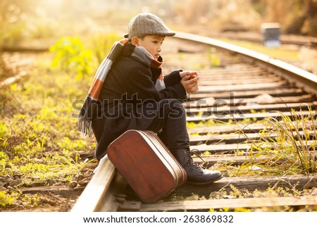 Adorable boy on a railway station - stock photo