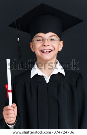 Adorable boy wearing black graduation gown holding diploma - stock photo