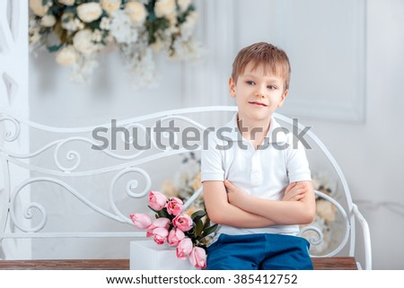 Adorable boy with a bouquet of pink tulips, Mother's Day, 8 March - stock photo