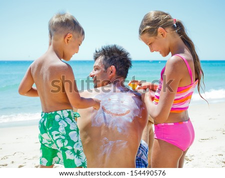 Adorable boy with his sister at tropical beach applying sunblock cream on a father's back. - stock photo