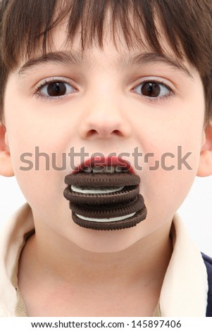 Adorable Boy with Mouth Full of Cream Stuffed Cookies - stock photo