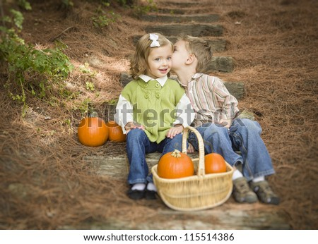 Adorable Brother and Sister Children Sitting on Wood Steps with Pumpkins Whispering Secrets or Kissing Cheek. - stock photo